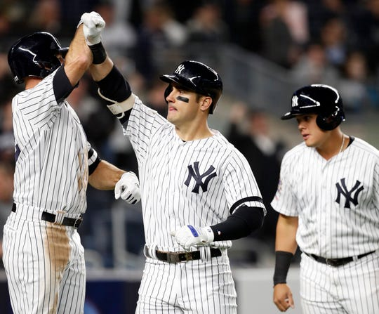 New York Yankees' Brett Gardner, left celebrates with the Mike Tauchman after Tauchman hit a sixth-inning, three-run home run off Boston Red Sox's Erasmo Ramirez during a baseball game Tuesday, April 16, 2019, in New York. Yankees' Gio Urshela, right, scored on the homer, as did Gardner.