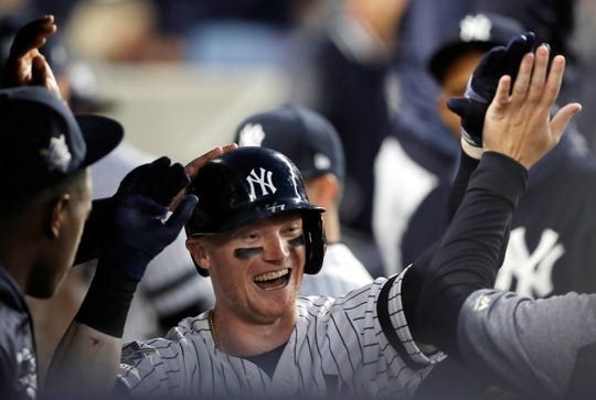 New York Yankees' Clint Frazier is congratulated in the dugout after hitting a solo home run off Boston Red Sox starting pitcher Chris Sale during the fourth inning of a baseball game Tuesday, April 16, 2019, in New York.