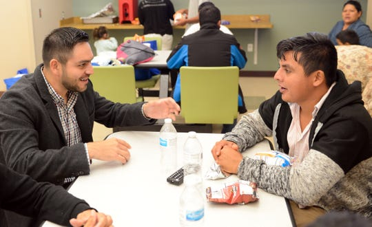 Las Cruces City Council member Gabe Vasquez speaks with a migrant at the Doña Ana County Crisis Triage Center on Wednesday, April 17, 2019.