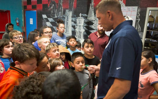 Dan O'Brien shows off his Olympic gold medal to children at the Las Cruces Boys and Girl's Club, Wednesday April 17, 2019. O'Brien won the decathlon at the 1996 Atlanta Games.