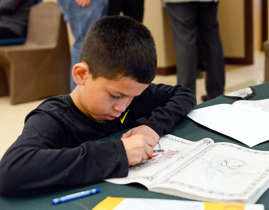 A young migrant boy colors a Spider-man coloring book at the Doña Ana County Crisis Triage Center, which has been converted into a temporary shelter for asylum seekers, on Wednesday, April 17, 2019.