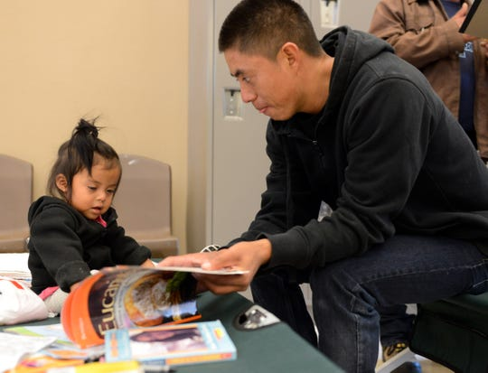 A migrant father shows a picture book to his young daughter at the Doña Ana County Crisis Triage Center on Wednesday, April 17, 2019.