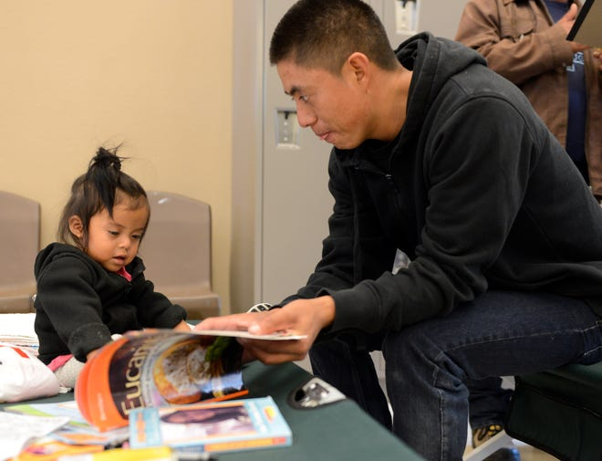A migrant father shows a picture book to his young daughter at the Doña Ana County Crisis Triage Center, which served as a temporary shelter for asylum seekers in the first days of a flood of asylum seekers released in the city of Las Cruces, on Wednesday, April 17, 2019.
