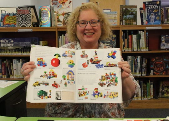 Beth Nieman, the Youth Services Librarian in Carlsbad, shows one of the library's book on LEGO structures.