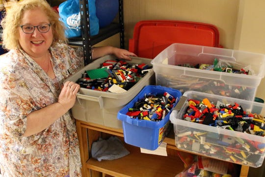 Beth Nieman shows off the four large boxes of LEGOs that she keeps in reserve in case more people show up to the weekly LEGO Club than originally planned.