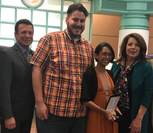 Tiana Huerta, 24, of La Quinta, second from right, was honored Tuesday, April 16, 2019, at City Hall for stopping to help a man attempting to jump off a bridge in November. She is standing with Councilman Robert Radi, from left, her boyfriend, Lawrence Devora, and Mayor Linda Evans.