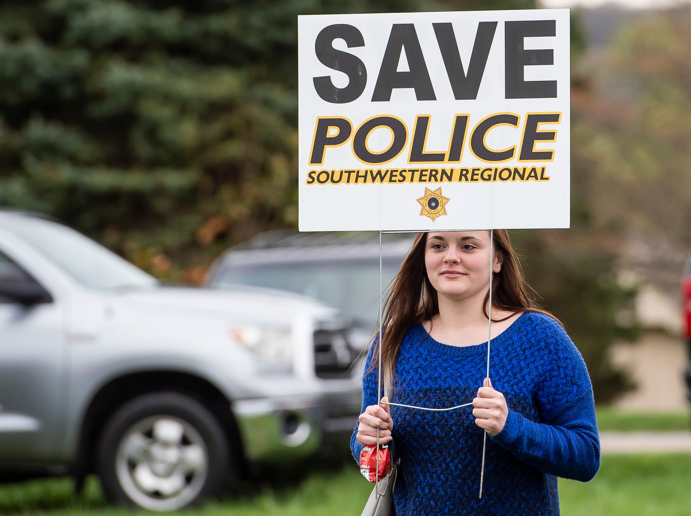 Brooklyn Blymier carries a sign in support of Southwestern Regional Police before the start of a North Codorus Township meeting on Tuesday, April 16, 2019.