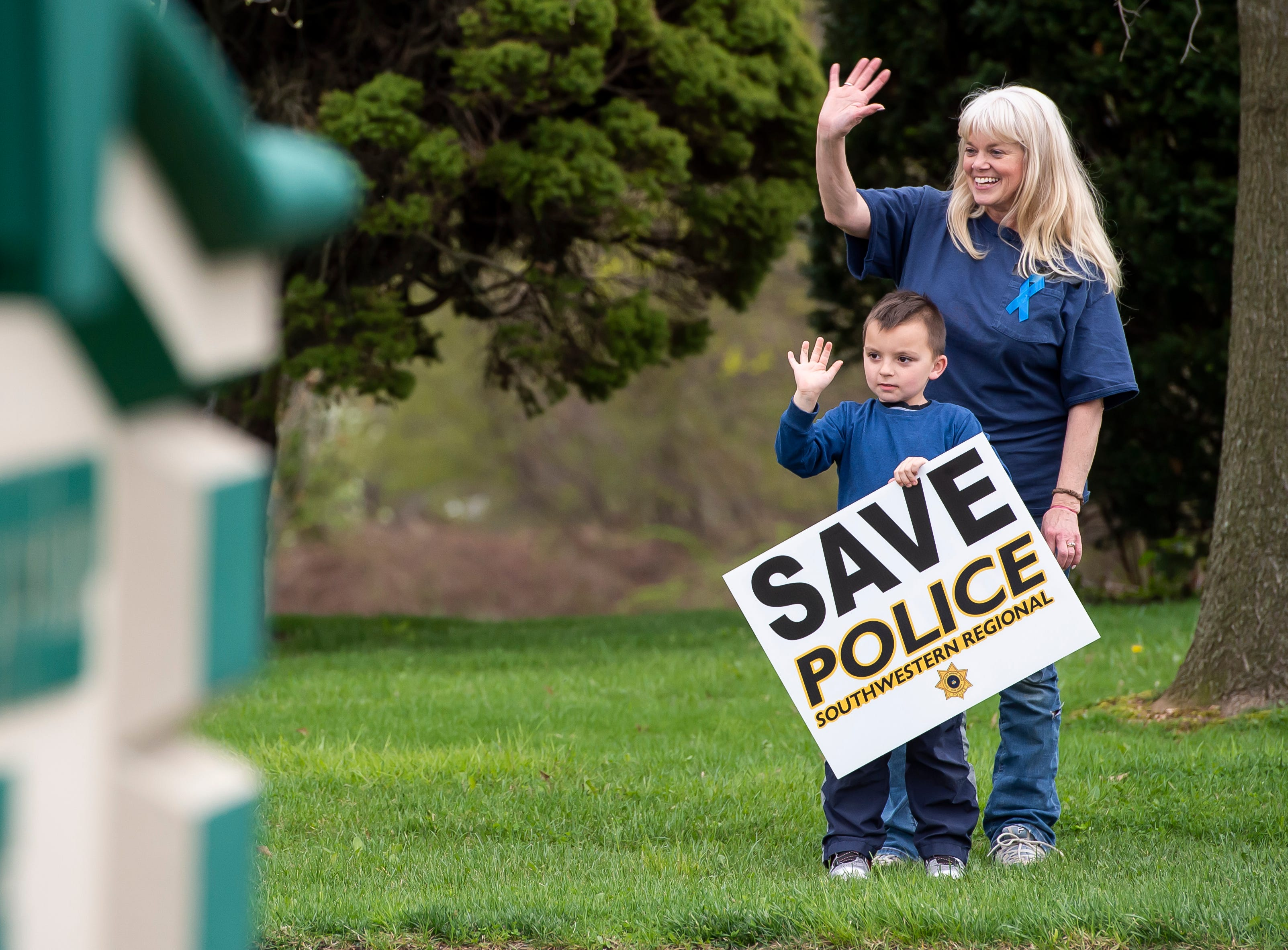 Linda Ziegler and her son, Jackson Ziegler, 7, wave to passing cars as they demonstrate in support of Southwestern Regional Police across the road from the North Codorus Township building on Tuesday, April 16, 2019.