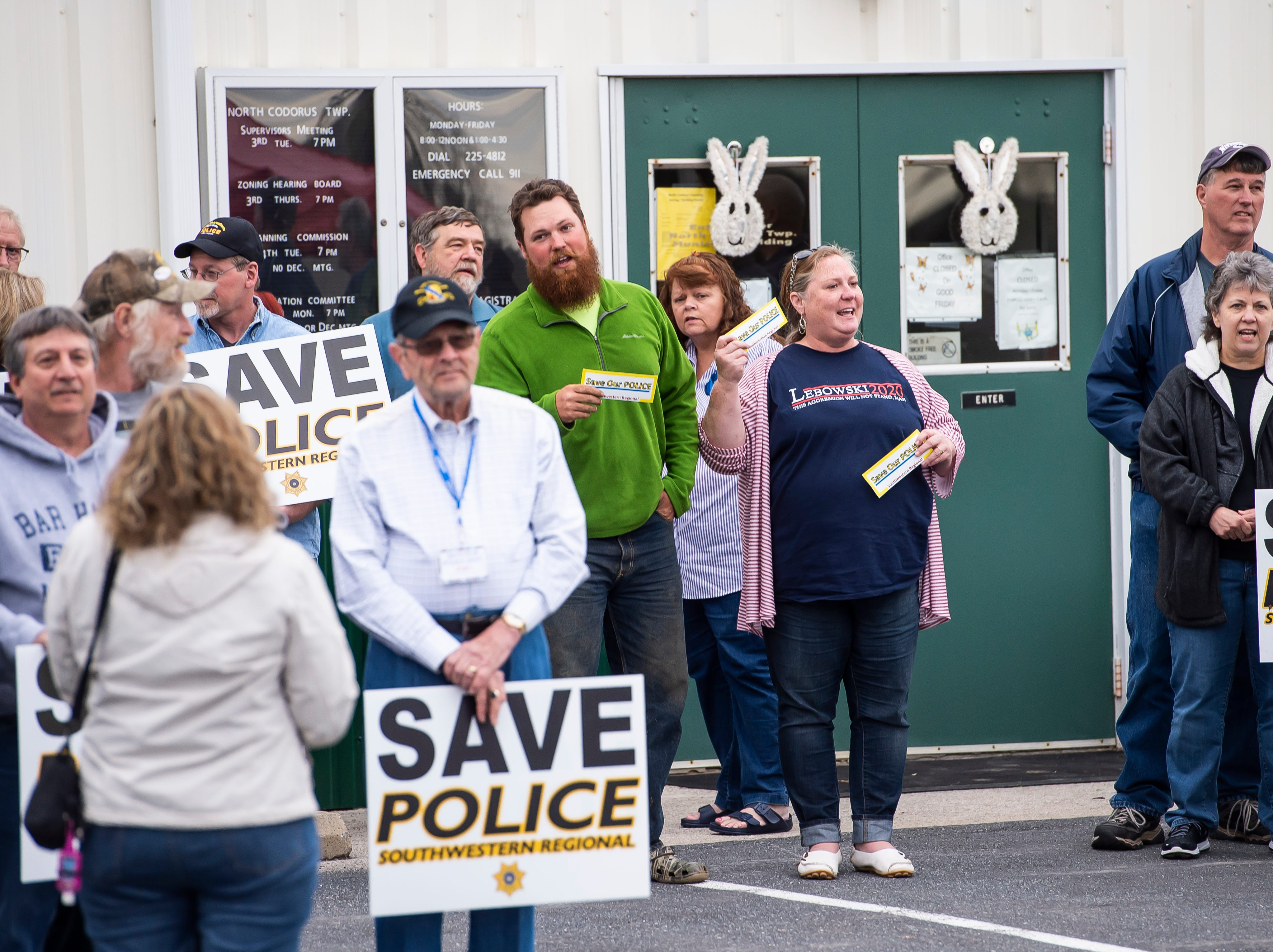 """North Codorus Township residents chant """"Save our police"""" before the start of a township meeting on Tuesday, April 16, 2019."""
