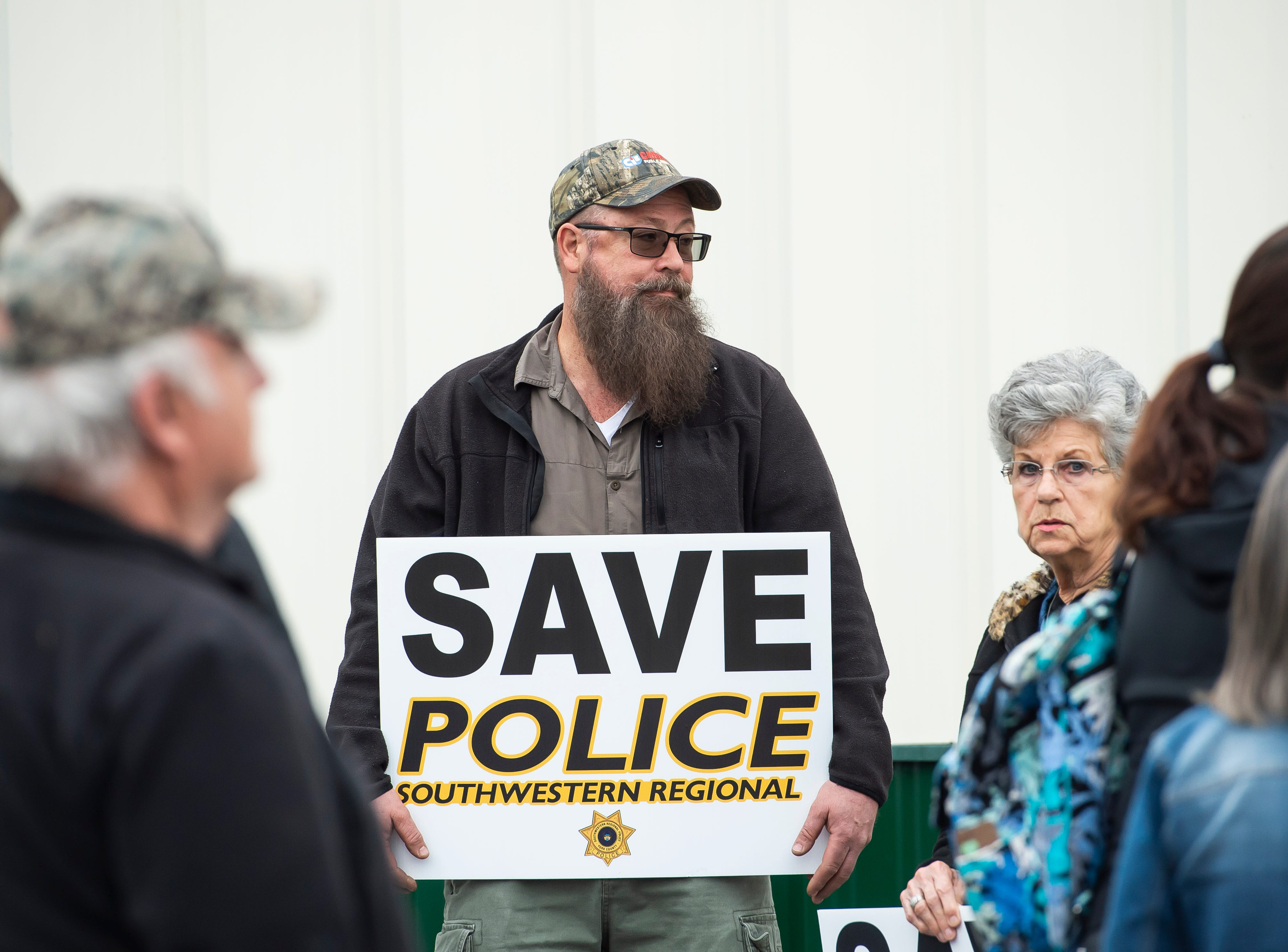 Brad Miller holds a sign showing his support for the Southwestern Regional Police Department before the start of a North Codorus Township meeting on Tuesday, April 16, 2019.