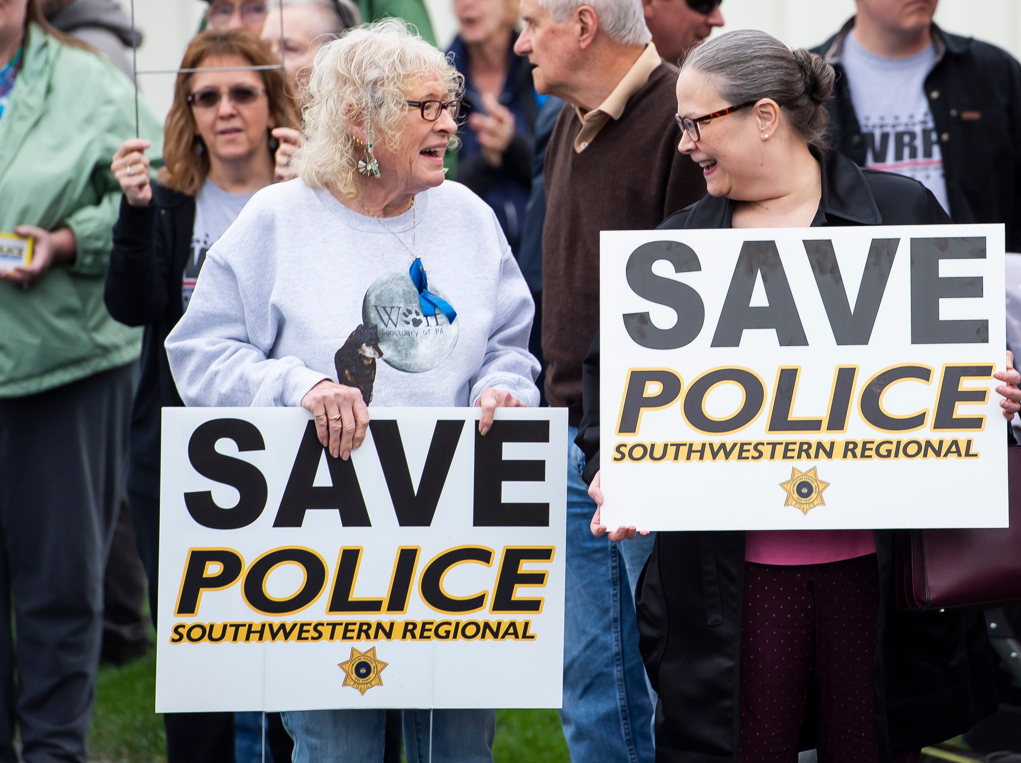 Becky Keagy, left, and Kathy Best hold signs in support of Southwestern Regional Police before the start of a meeting at the North Codorus Township building on Tuesday, April 16, 2019.