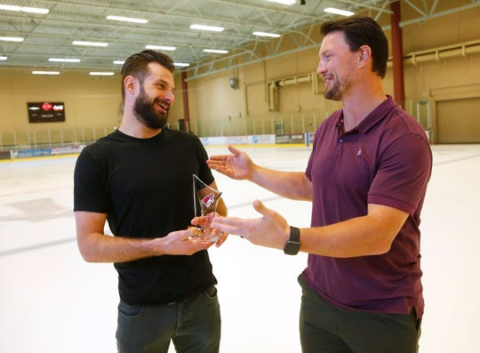 "Coyotes Brad Richardson (left) receives the ""Shane Doan Good Guy Award"" from Shane Down at the Ice Den in Scottsdale, Ariz. April 17, 2019. The inaugural award was given by the Arizona chapter of the Pro Hockey Writers' Association."