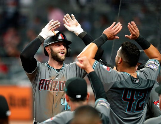 Arizona Diamondbacks' Christian Walker, left, celebrates as he returns to the dugout after hitting a solo-home run in the ninth inning of a baseball game against the Atlanta Braves, Tuesday, April 16, 2019, in Atlanta.