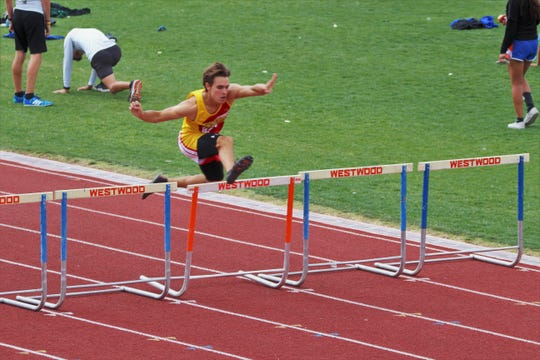 Seton Catholic senior Nick Wade completes in the 300 meter hurdles.