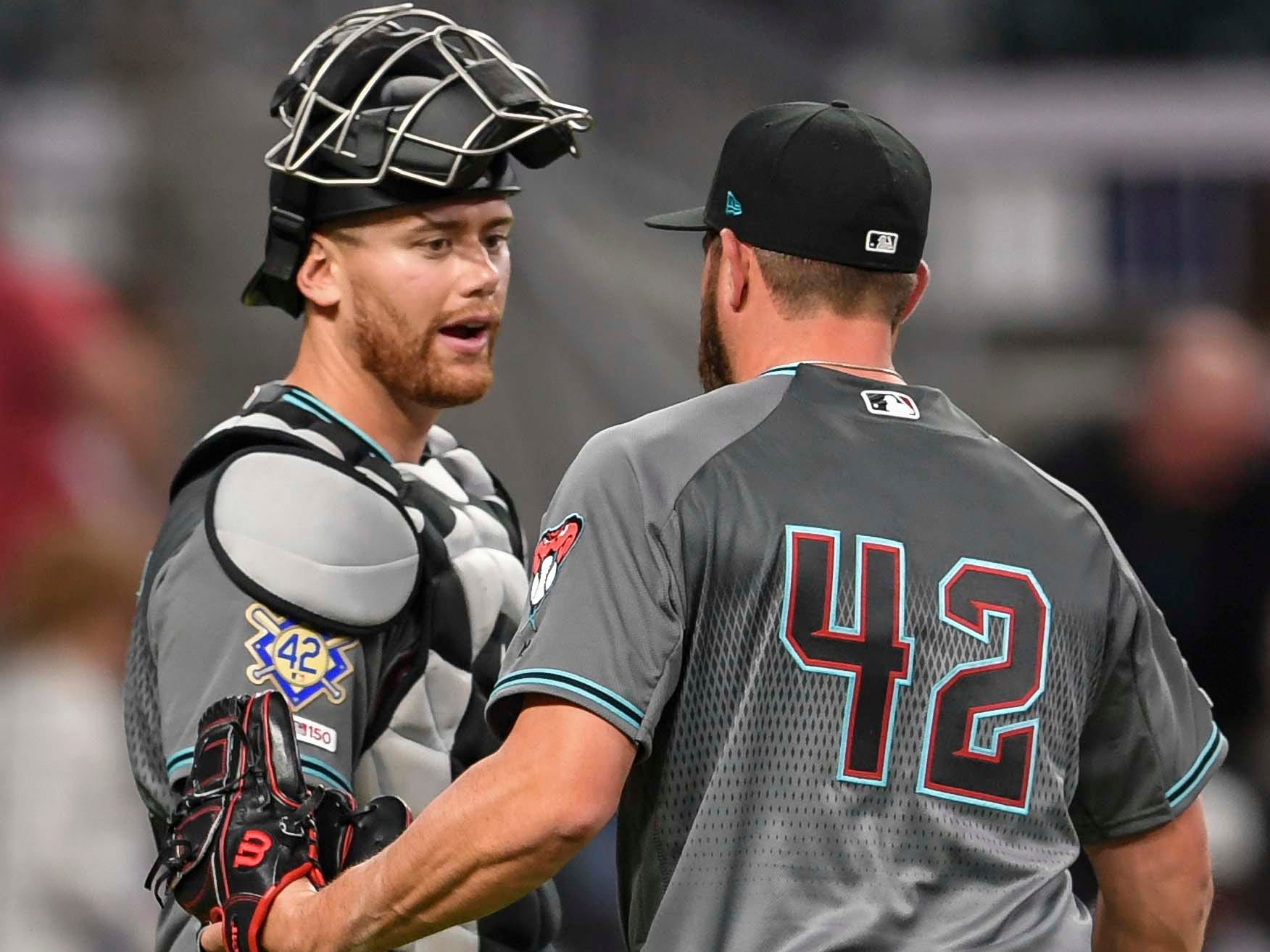 Apr 16, 2019; Atlanta, GA, USA; Arizona Diamondbacks relief pitcher Greg Holland (56) reacts with catcher Carson Kelly (18) after defeating the Atlanta Braves at SunTrust Park. Mandatory Credit: Dale Zanine-USA TODAY Sports