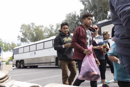 Guatemalan national Modesto Martin-Diaz, 33, (on left) with his son Edgar, 16, arrives in an ICE bus with other asylum seekers at at the church.
