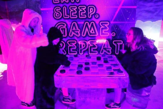 Chloe Regis (izquierda), Jesika Sutton (centro) y Sidney McNeal juegan a las damas chinas en el Polar Play Ice Bar en Scottsdale.