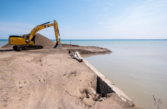 Construction equipment sits on the banks at the edge of the Black River canal Wednesday, April 17, 2019 in Port Huron. Crews are dredging excess sand from the mouth of the canal and placing it along a small public beach at the end of Holland Avenue on Lake Huron.