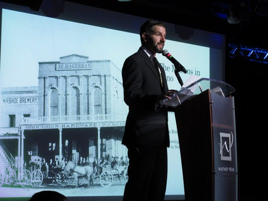 The Reno Masonic Lodge built in 1872 is shown on a screen behind Nathan Digangi, worshipful master of Reno Lodge #13, as he speaks Tuesday, April 16, 2019, in Reno, Nev., at the unveiling of a time capsule found inside the recently demolished building. Artifacts inside included silver dollars minted in Carson City and San Francisco and a piece of wood from Sutter's Mill where the discovery of gold in 1848 sparked the California Gold Rush. (AP Photo/Scott Sonner)