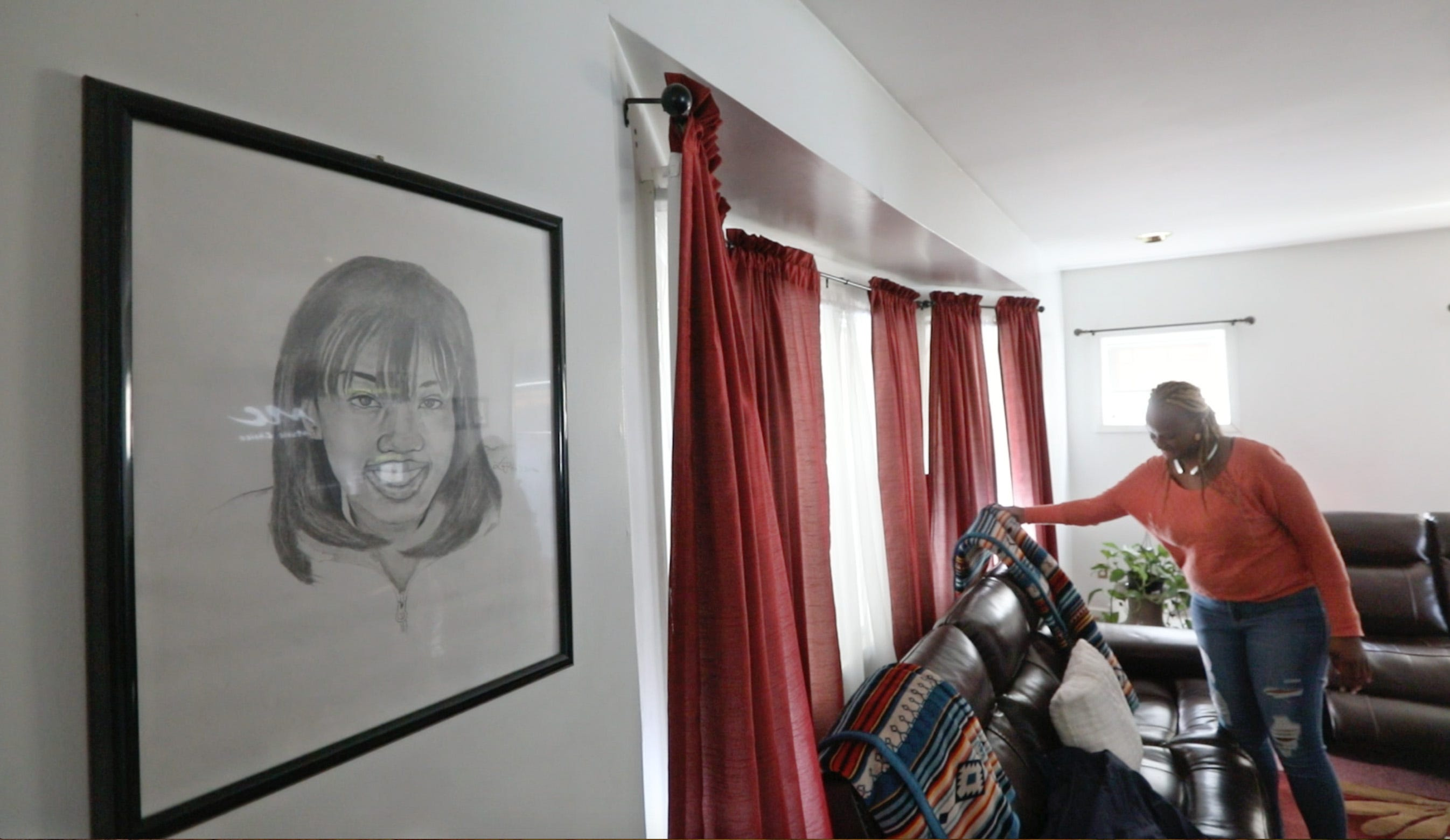 Tawana Wyatt, mother of India Cummings, straightens her living room as a portrait of India looks over her in her Rochester home Friday, March 1, 2019.