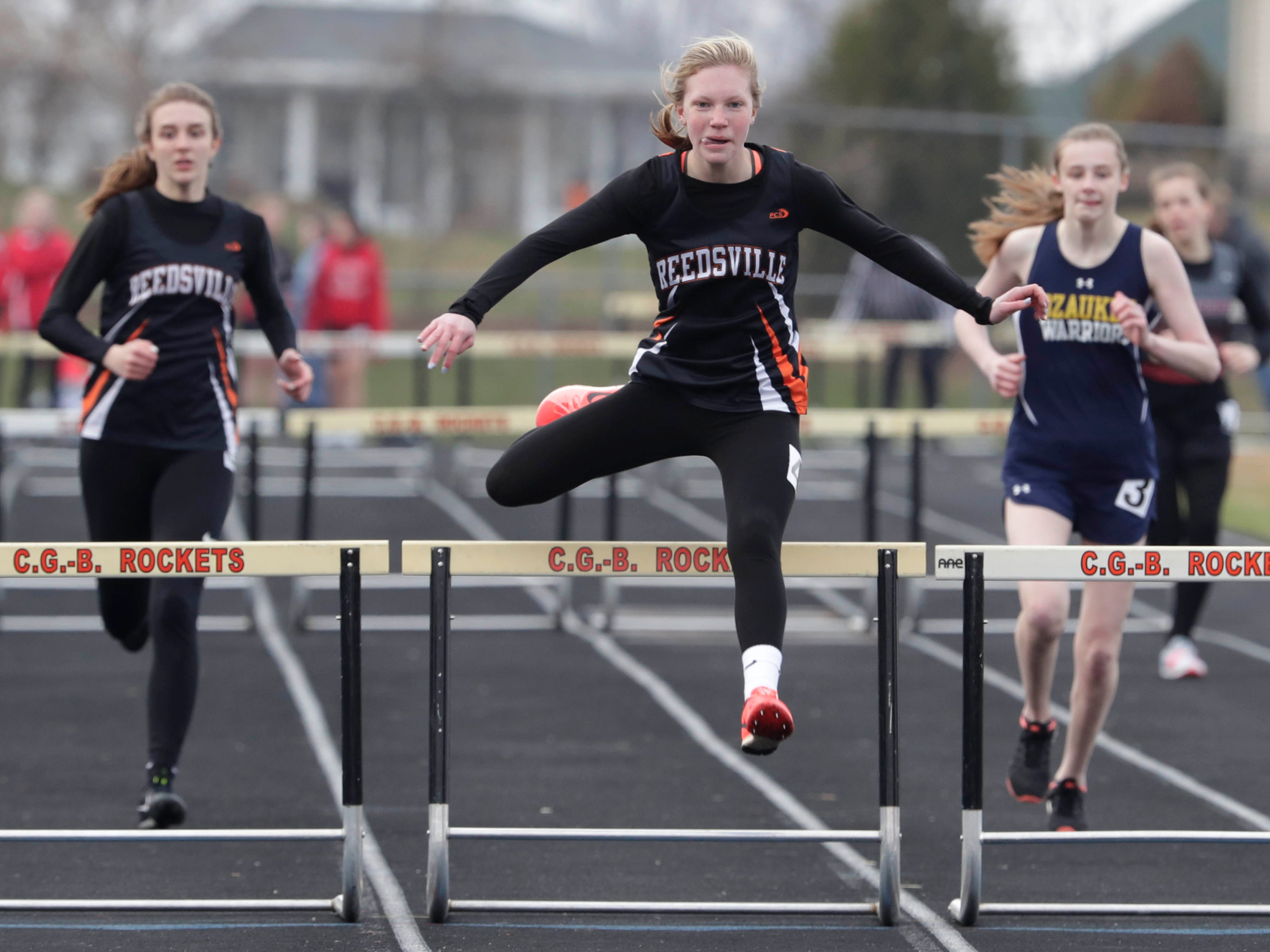 Reedsville's Katlyn Larson, center, led the way for the 300 meter hurdles, Tuesday, April 16, 2019, in Cedar Grove, Wis. At left is Rachel Peterson and at right is Ozaukee's Sarah Nehls.