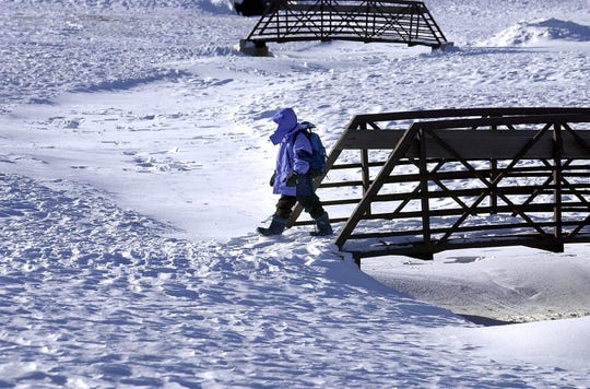A John F. Kennedy student is bundled up from head to toe as he crosses a footbridge into a snow covered field after school Monday as temperatures in the teens chilled the Sioux Falls area. On Nov. 21, 2000. School closures because of snow were harder to come by then.