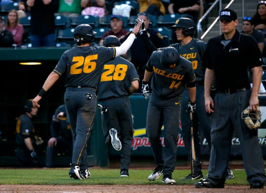 Mizzou's Trevor Mallett high fives a teammate after scoring during a 5-run third inning as the Tigers took on the Missouri State Bears at Hammons Field on Tuesday, April 16, 2019.