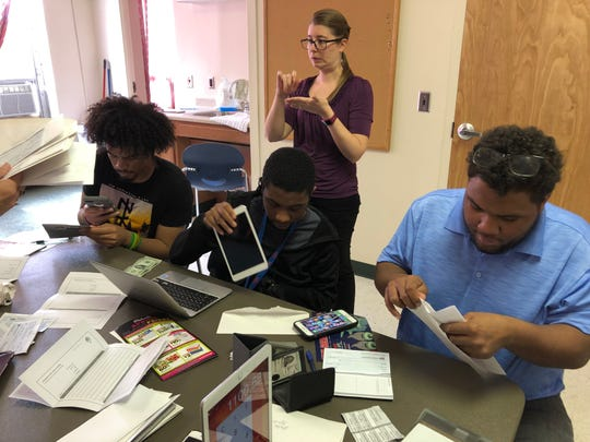 Students in the Virginia School for the Deaf and the Blind's independent living program learn about paychecks and bills on April 17, 2019.