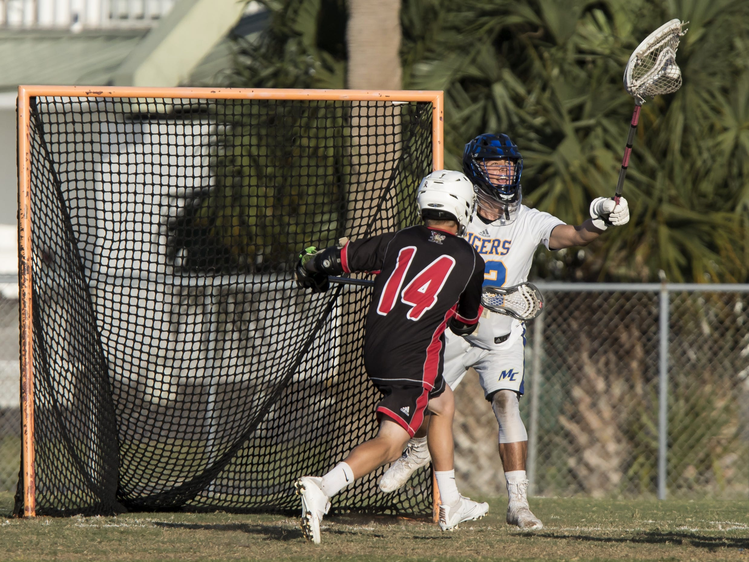 Martin County goalie James Crighton (right) catches Vero Beach player Cameron Smith's shot during the high school boys lacrosse game Tuesday, April 16, 2019, at the Citrus Bowl in Vero Beach.