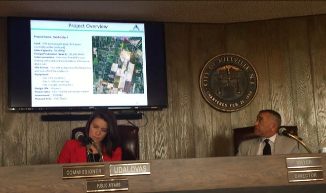 Solar power developers presented Millville officials on Tuesday with a proposal for a 50-megawatt station off Nabb Avenue. Mayor Michael Santiago (right) looks here at a project overview from Dakota Power Partners.