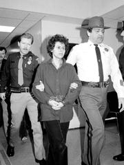 Weather Underground member Judith Clark, 31, is handcuffed as she is escorted into Rockland County Courthouse in New City, N.Y., Nov. 24, 1981. She was arraigned on 13 counts in connection with an Oct. 20 robbery of a Brink's armored truck which left two police officers and a Brink's guard dead.