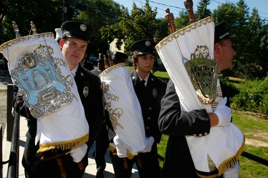 In August 2010, West Clarkstown Jewish Center in New City rededicated their synagogue that was severely damaged in a fire the year before. From left, Hillcrest firefighters Matthew Boney, Danny Assaban and Lt. Gregory Martin carry three torahs that firefighters rescued from the blaze.