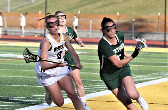 Yorktown's Jesse Barer (r) carries the ball up the sideline after grabbing it off draw. Emma Halderman of Lakeland/Panas (l) pursues during April 17, 2019 game.