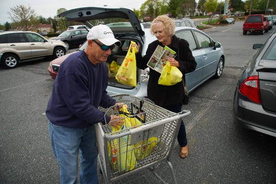 Oscar and Janet Schweizer, of Richardson Park, unload plastic bags full of groceries into their nearby car after shopping at the ShopRite in Newport.