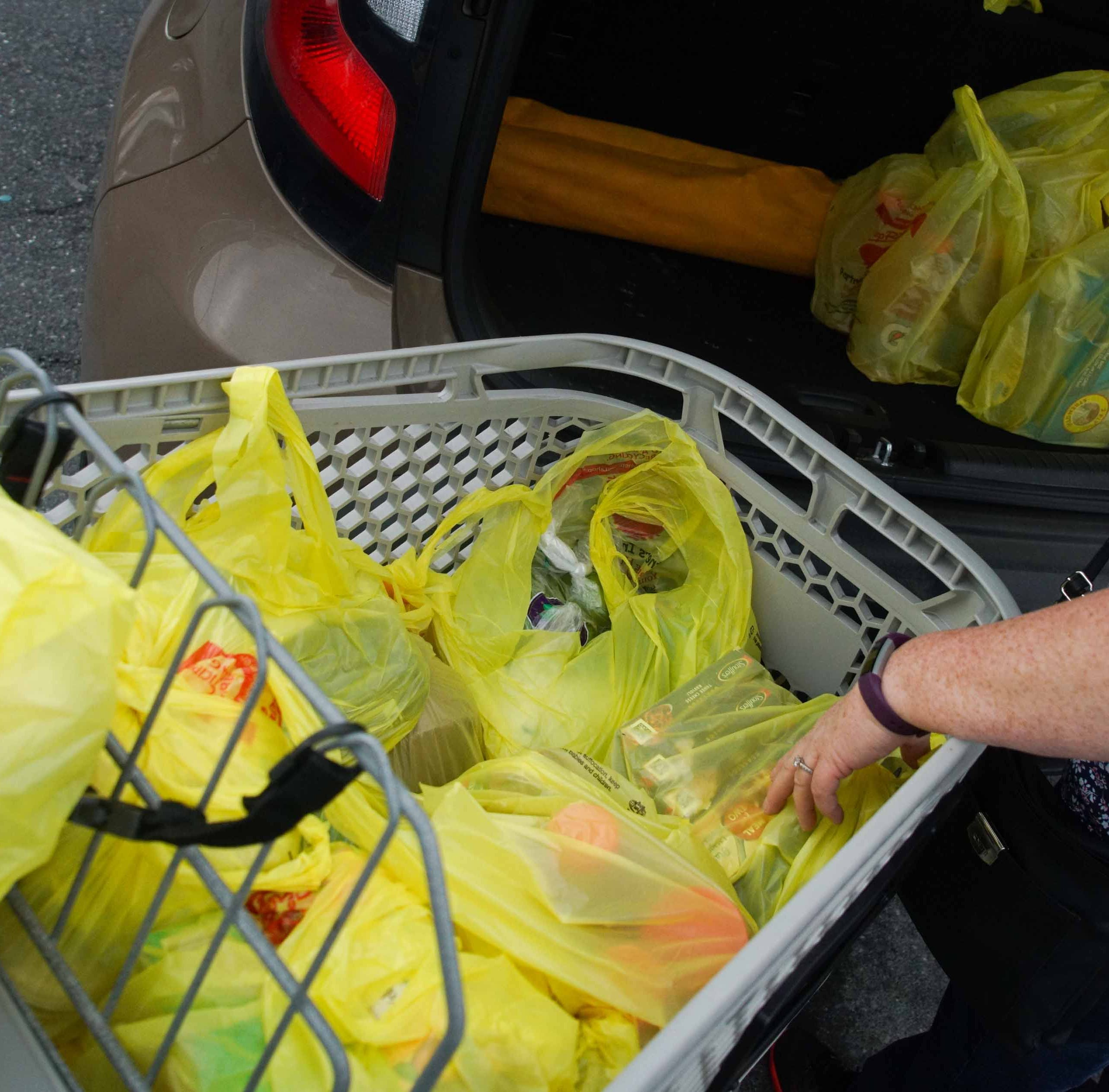 A customer of the ShopRite in Newport unloads bags of groceries on Wednesday.