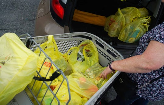 A ShopRite customer in Stanton unloads bags of groceries. If a Delaware bill passes, more than 3,600 businesses would have to stop giving out plastic bags at check-out, according to the state Department of Natural Resources and Environmental Control.