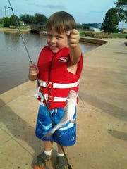 In this picture from a couple years ago, Fisher Lang shows off a catfish he caught at South Weeks Pond.