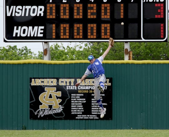 Justin Browning's homerun passes Windthorst's Kyle Wolf and bounces off the Archer City scoreboard Tuesday, April 16, 2019. The Trojans defeated the Wildcats 4-3 in the first game of the doubleheader.