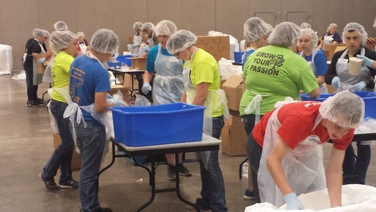 FFA members volunteer their time to package food.