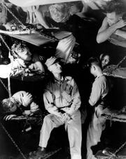 Ernie Pyle, center, talks with Marines below decks on a U.S. Navy transport while en route to the invasion of Okinawa in this March 1945 file photo.