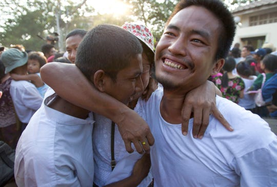 Two men are celebrated by their mother, center, after being released from Insein prison April 17, 2019, in Yangon, Myanmar. More than 9,500 prisoners were ordered released Wednesday in Myanmar under a presidential amnesty, but they did not include two Pulitzer Prize-winning Reuters reporters.