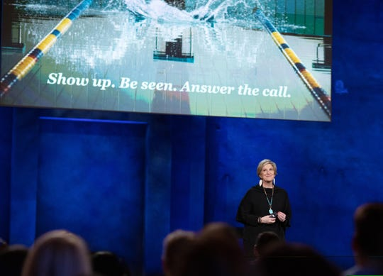 """Brené Brown stands in front a screen that begs people to """"Answer the call"""" during her Netflix special."""