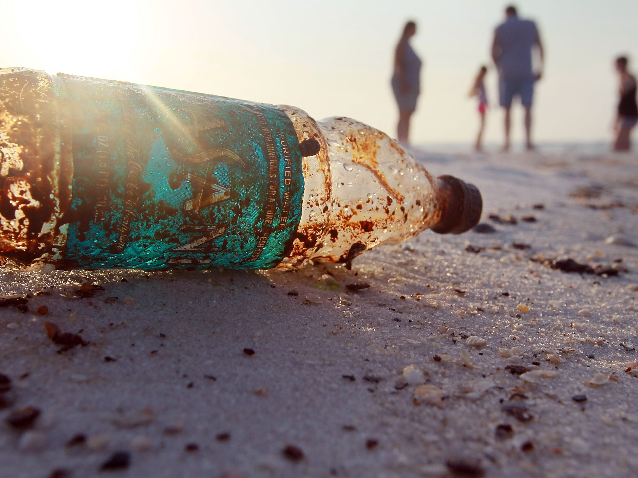 A plastic bottle is seen coated in oil on Pensacola Beach as oil makes its way on shore from the Deepwater Horizon oil spill in the Gulf of Mexico on June 6, 2010 in Pensacola, Fla.