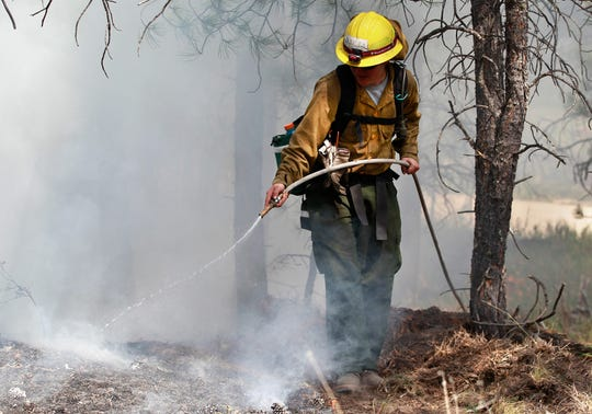 An AmeriCorps volunteer firefighter sprays water to contain a spot fire in an evacuated area of residences, forest, and ranches in the Black Forest wildfire area, north of Colorado Springs, Colo., on June 13, 2013.
