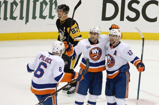 First round: New York Islanders defenseman Ryan Pulock (6) and forwards Valtteri Filppula (51) and Josh Bailey (12) celebrate an empty net goal in the Game 4 series-clinching win vs. the Pittsburgh Penguins