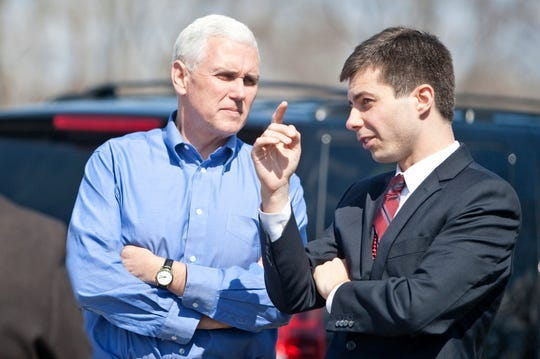 In this April 1, 2013 photo, Indiana Gov. Mike Pence, left, speaks to South Bend Mayor Pete Buttigieg following a Dyngus Day event in South Bend, Ind.