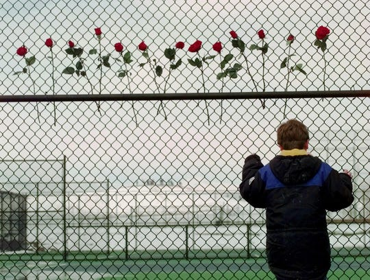 A boy looks through the fence at the Columbine High School tennis courts on April 24, 1999. Thirteen roses were placed on the fence in remembrance of the 13 people killed by two gun-wielding students at the school.