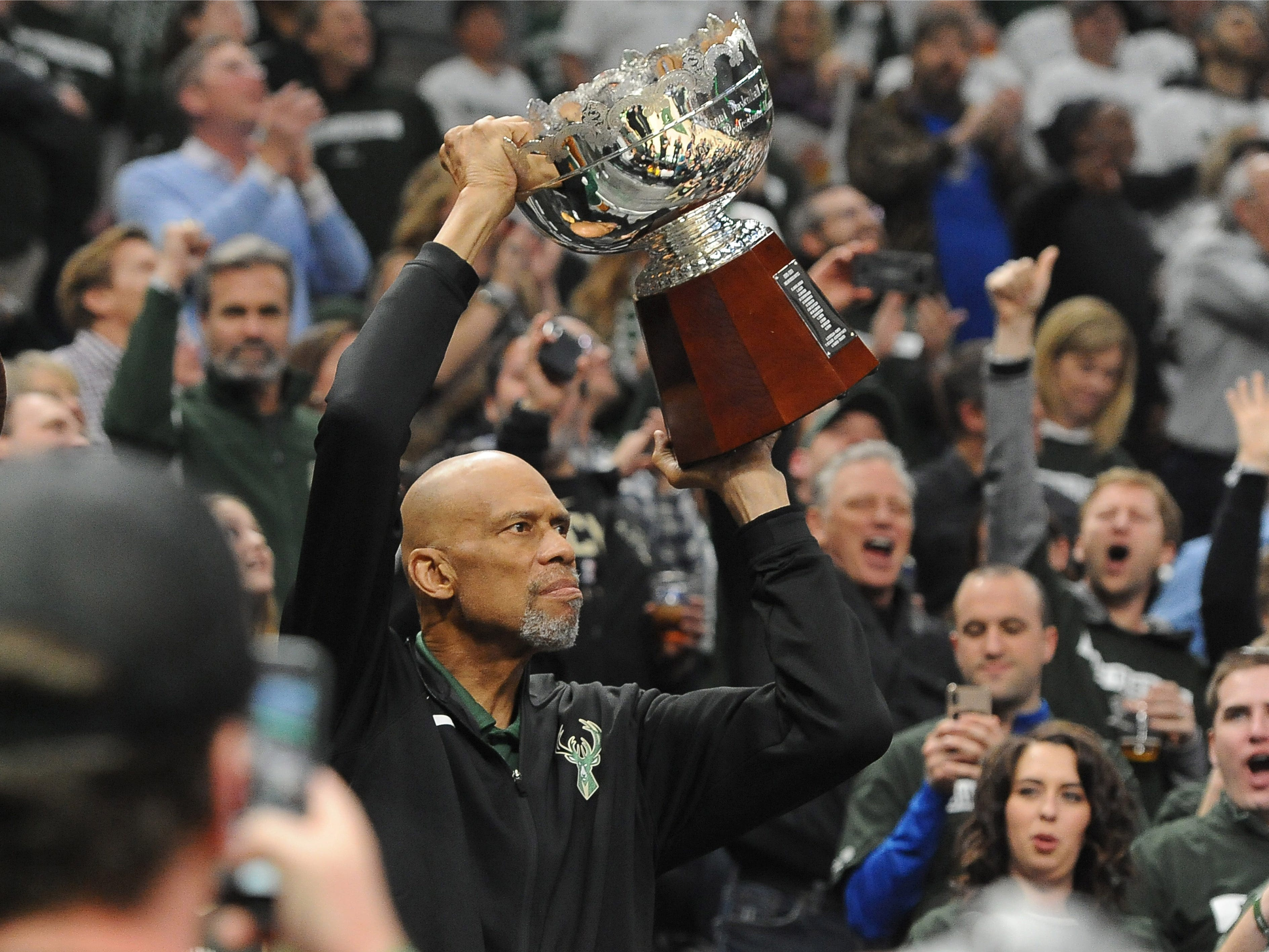 April 14: Hall of Famer Kareem Abdul-Jabbar holds up the 1971 championship trophy during a break in Game 1 between the Bucks and Pistons in Milwaukee.