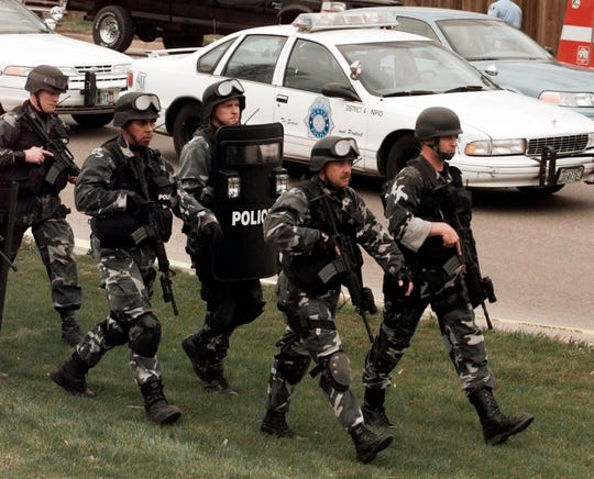 Members of a police SWAT team march to Columbine High School in Littleton, Colo., as they prepare to do a final search of the school on April 20, 1999.