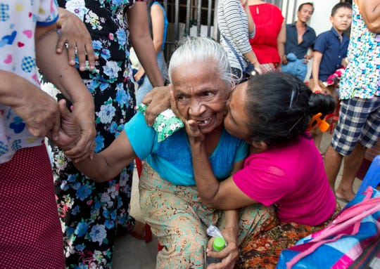 An elderly woman, center, is hugged by her colleague after being released from Insein prison April 17, 2019, in Yangon, Myanmar. More than 9,500 prisoners were ordered released Wednesday in Myanmar under a presidential amnesty, but they did not include two Pulitzer Prize-winning Reuters reporters.